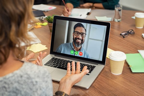Portrait of smiling man video conferencing on laptop with businesswoman. Casual woman video conferencing with mature middle eastern businessman on laptop. Happy man in video call with colleague over laptop.